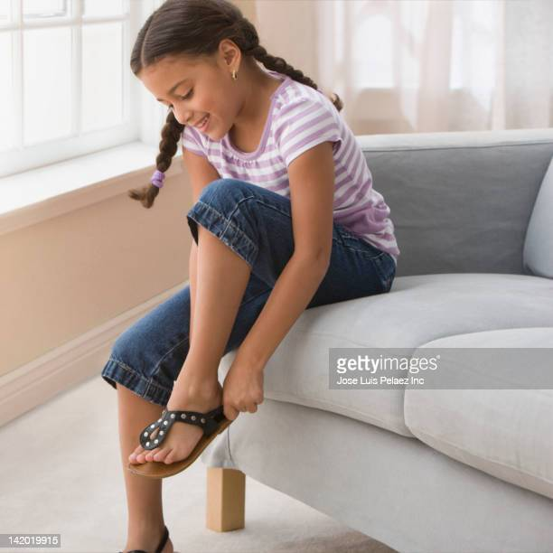 Hispanic girl putting on sandals