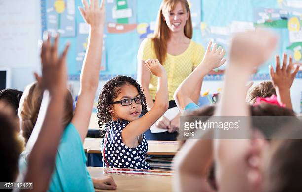 Hispanic girl raising hand in class