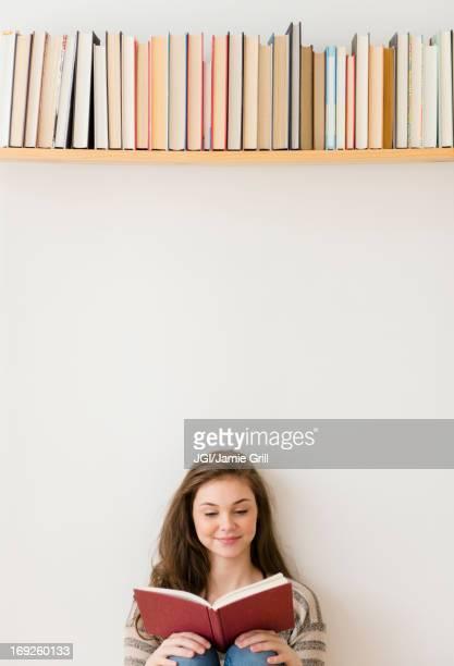 Hispanic girl reading under bookshelf