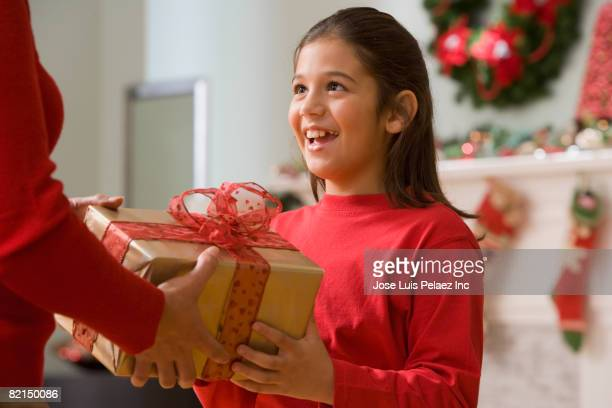hispanic girl receiving christmas gift - receiving stock pictures, royalty-free photos & images