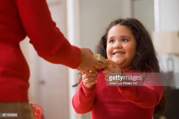 Hispanic girl receiving Christmas gift