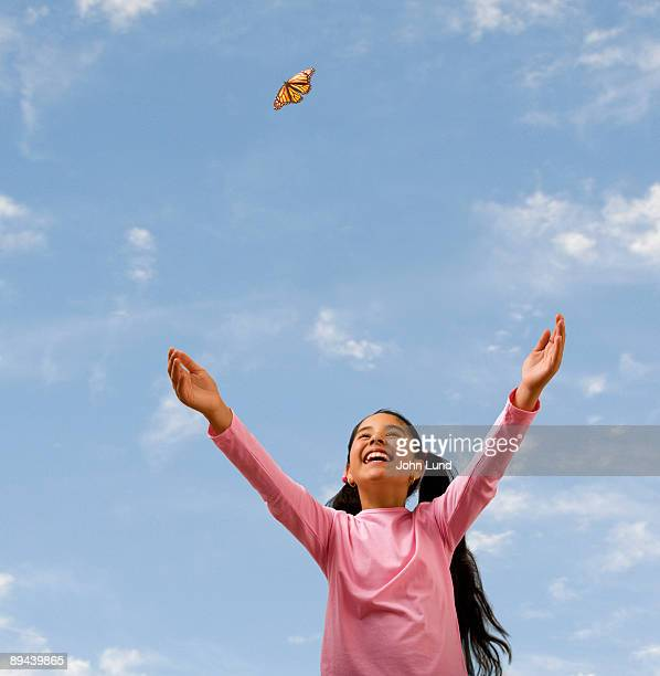 Hispanic girl releases butterfly