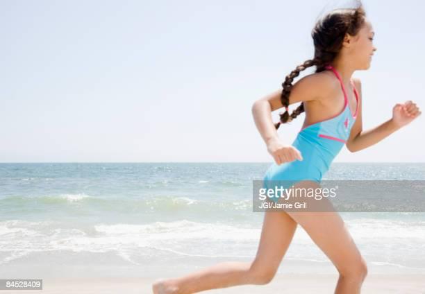 Hispanic girl running on beach