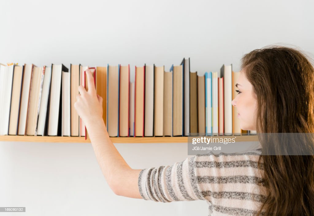 Hispanic girl selecting book from shelf : Stock Photo