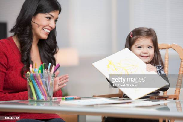 hispanic girl showing drawing to mother - la art show stock pictures, royalty-free photos & images