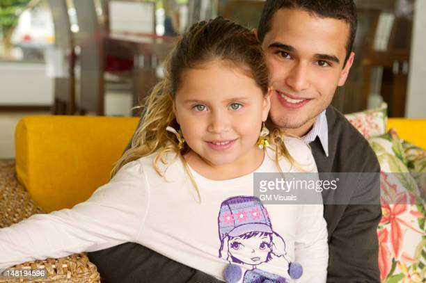 hispanic girl sitting on father's lap - niece stock pictures, royalty-free photos & images