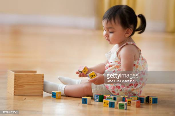 Hispanic girl sitting on floor playing with alphabet blocks