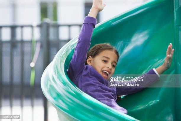 hispanic girl sliding down slide on playground - sliding stock pictures, royalty-free photos & images