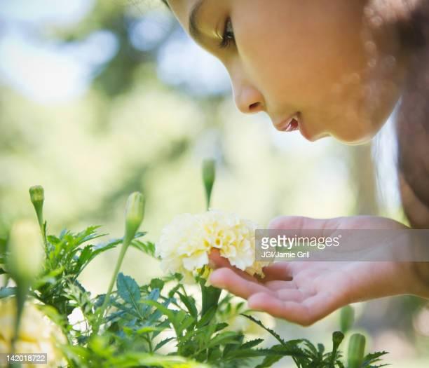 Hispanic girl smelling flower