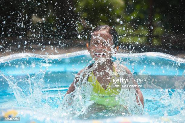 Hispanic girl splashing in kiddie pool