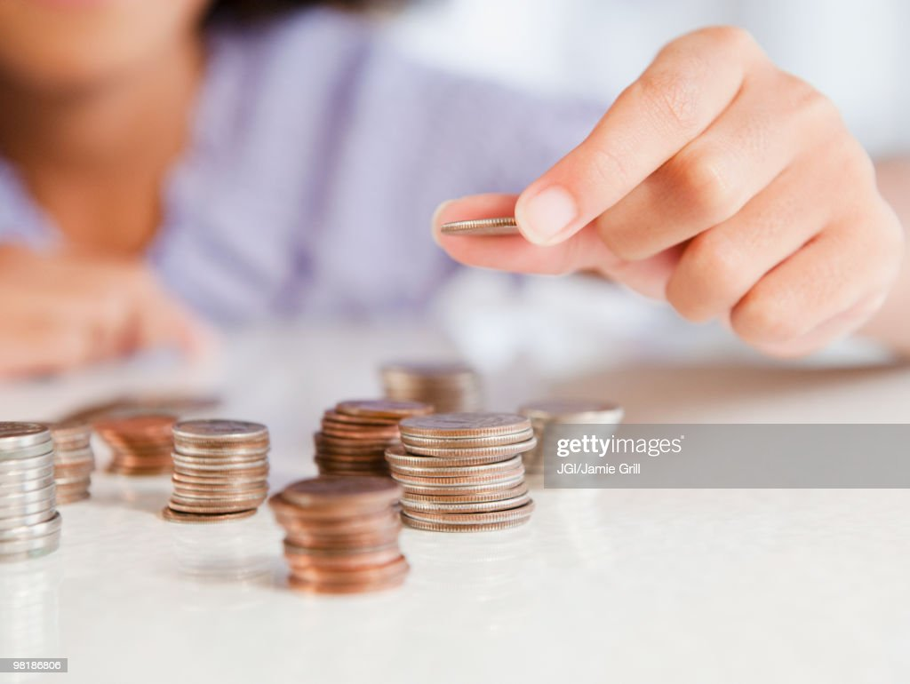 Hispanic girl stacking coins : Stockfoto