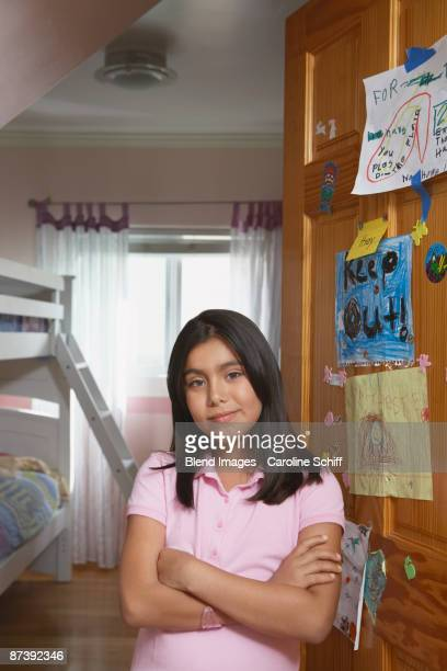 Hispanic girl standing in doorway with arms crossed