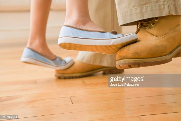Hispanic girl standing on father's toes