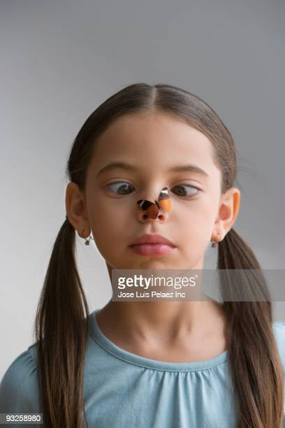 Hispanic girl staring cross-eyed at butterfly on nose