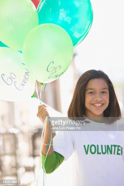 Hispanic girl volunteering and holding balloons
