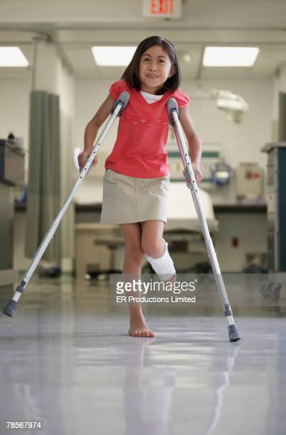 hispanic girl walking with crutches - crutches stock photos and pictures