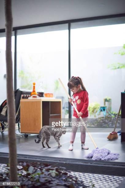 Hispanic girl watching cat and mopping floor