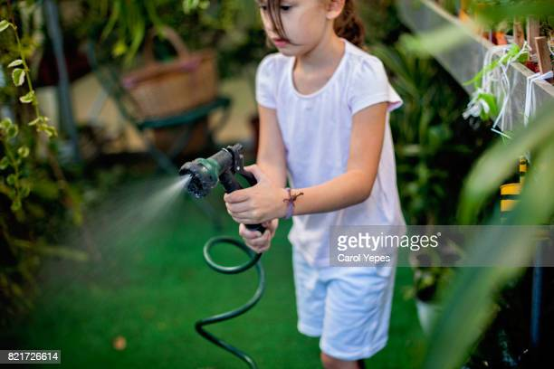 Hispanic girl watering plant and grass with hose
