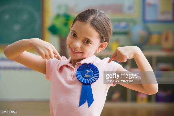 Hispanic girl wearing first place ribbon