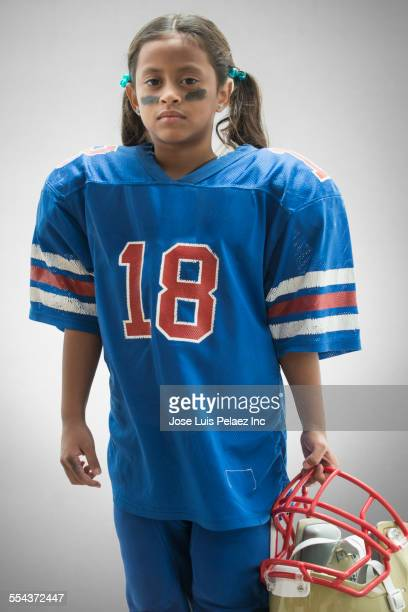 hispanic girl wearing football jersey and helmet - sports jersey stock pictures, royalty-free photos & images
