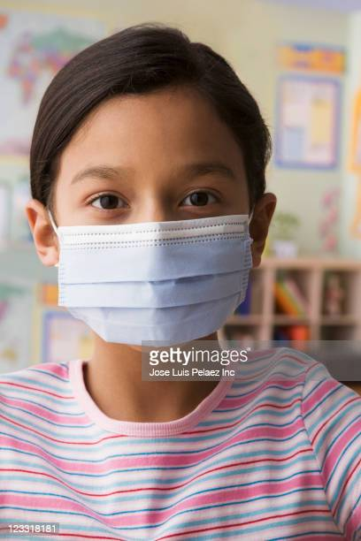hispanic girl wearing surgical mask - flu mask stock photos and pictures