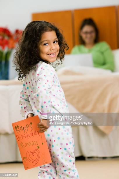 Hispanic girl with birthday card for mother