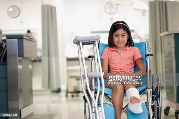 Hispanic girl with cast in wheelchair