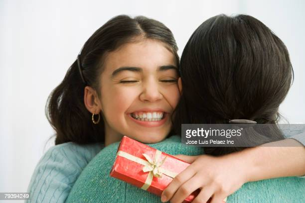 Hispanic girl with gift hugging mother