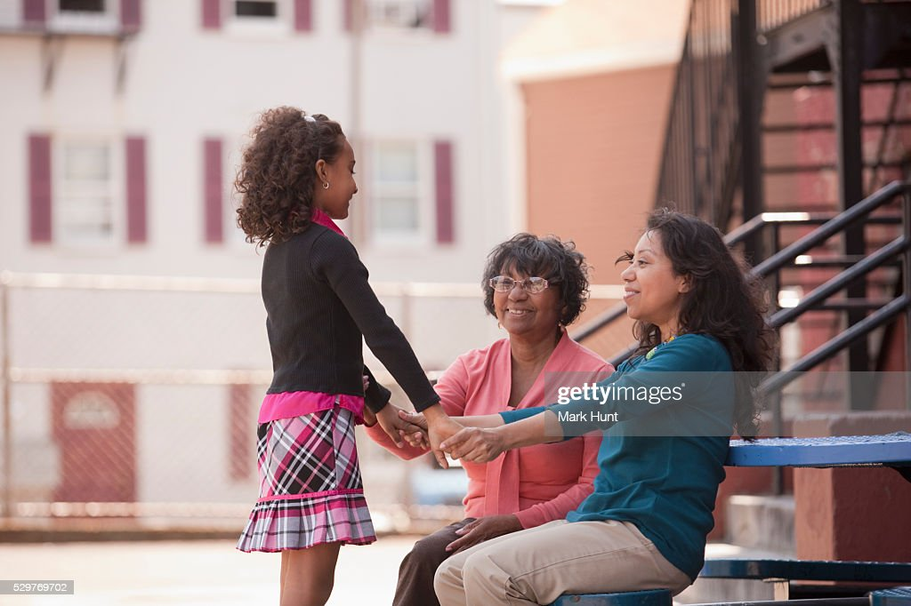 Hispanic girl with her mother and grandmother in the schoolyard : Stock Photo