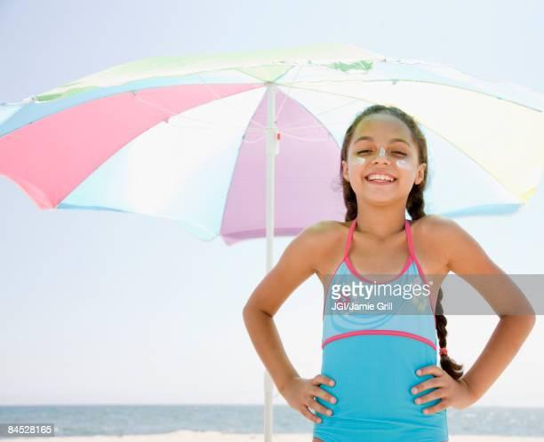 Hispanic girl with sunscreen under umbrella on beach