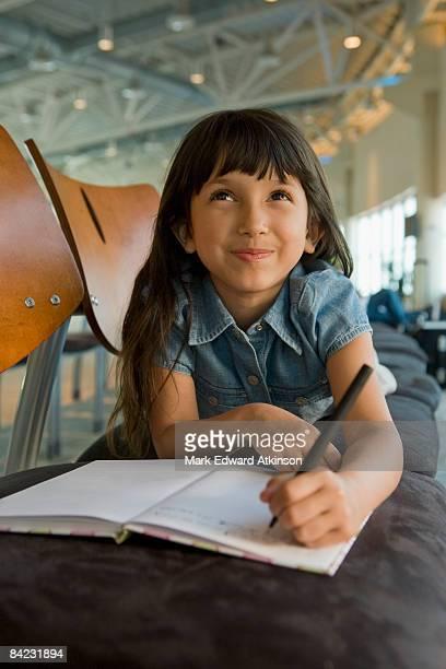 hispanic girl writing in diary in airport - 8 9 años fotografías e imágenes de stock
