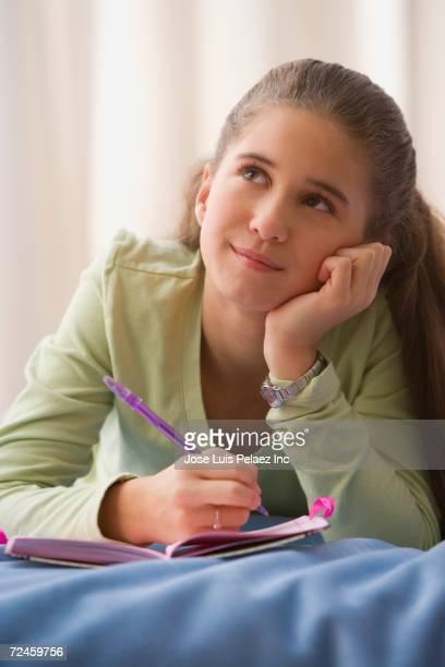 Hispanic girl writing in diary on bed