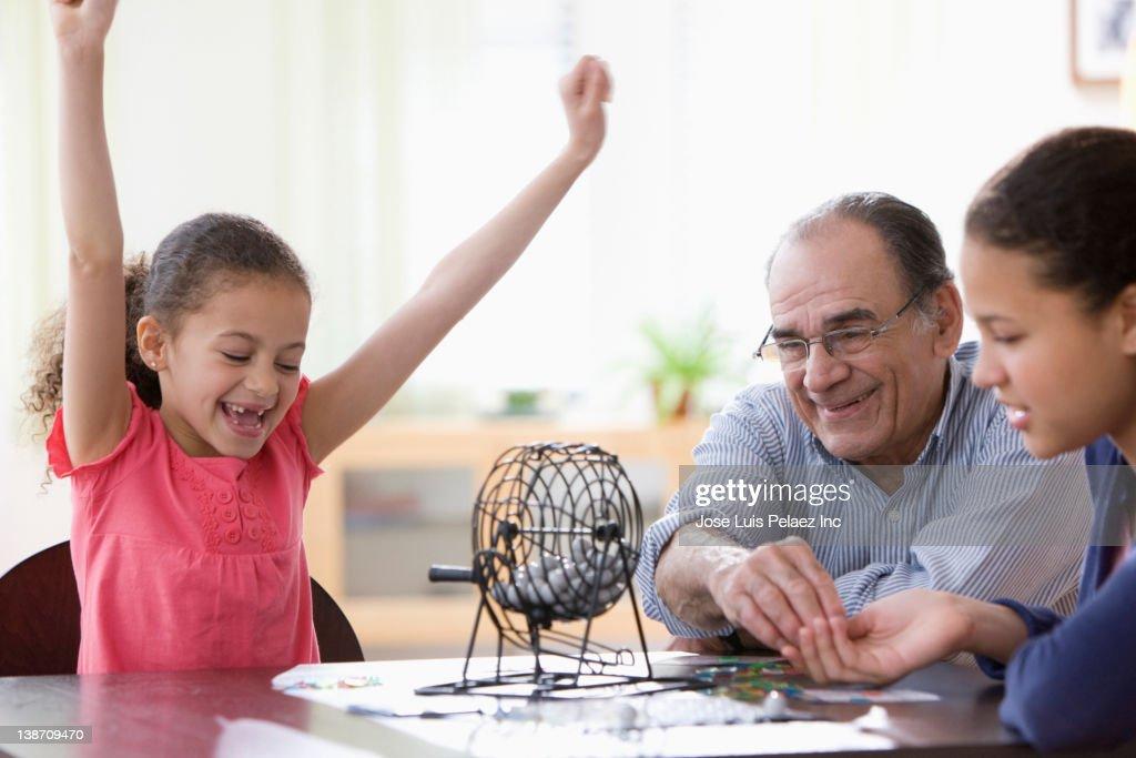 Hispanic girls and grandfather playing game : Stock Photo