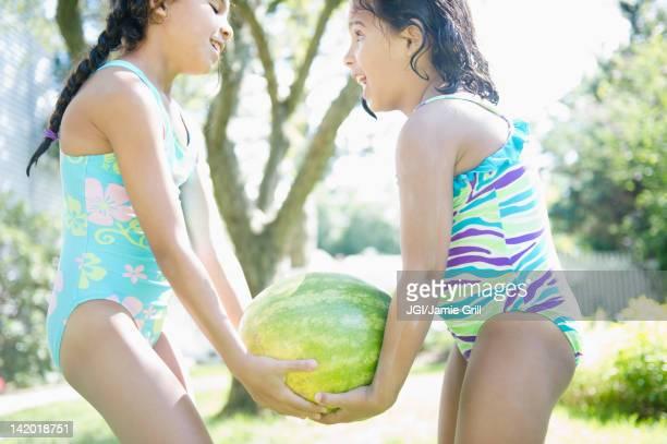 Hispanic girls carrying watermelon together