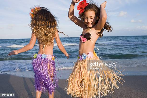 Hispanic girls dancing in hula skirts on beach