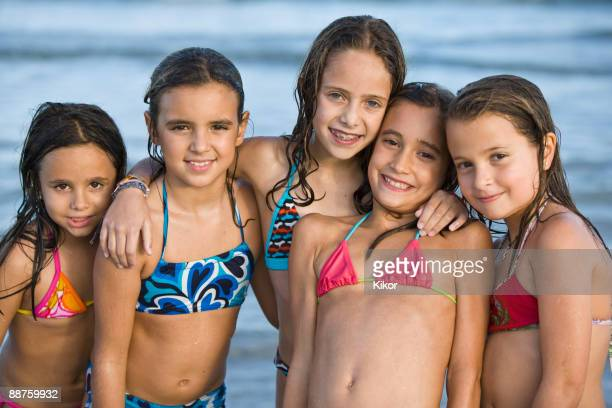 Hispanic girls in bikinis posing on beach