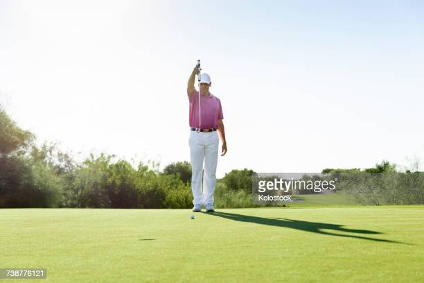 Hispanic golfer aiming on golf course