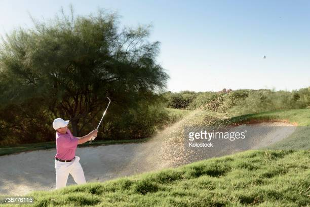 hispanic golfer hitting ball in sand trap - sand trap stock pictures, royalty-free photos & images