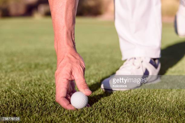 Hispanic golfer placing golf ball on tee