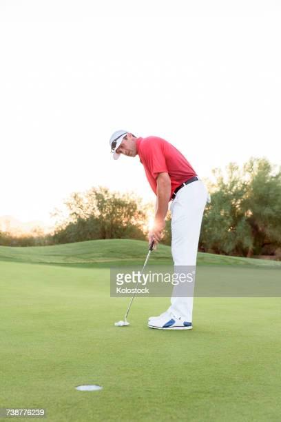 hispanic golfer putting on golf course - putting imagens e fotografias de stock