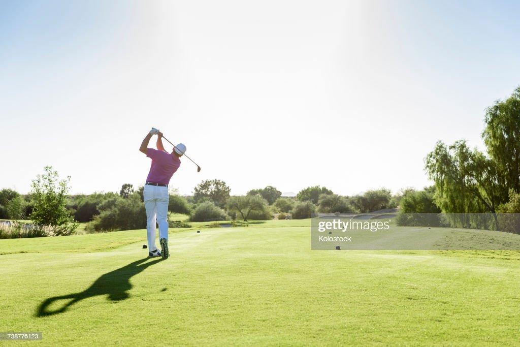 Hispanic golfer teeing off on golf course : Stock Photo
