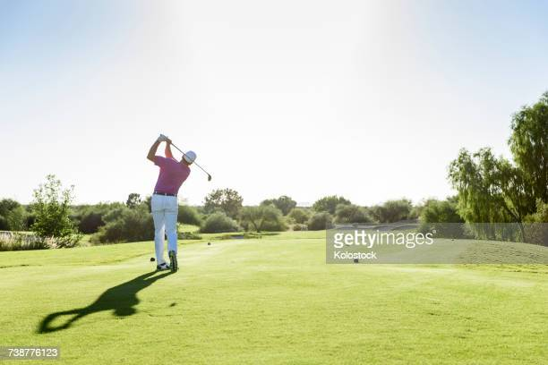 hispanic golfer teeing off on golf course - ゴルフ ストックフォトと画像