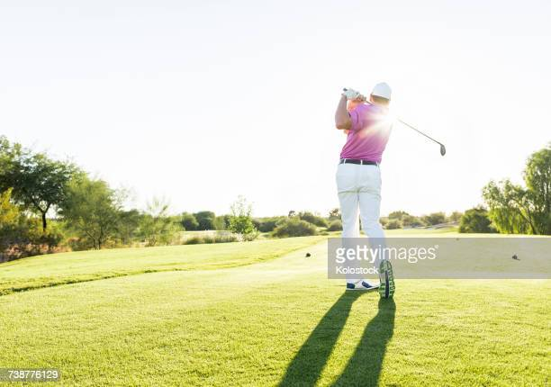 hispanic golfer teeing off on golf course - teeing off stock pictures, royalty-free photos & images