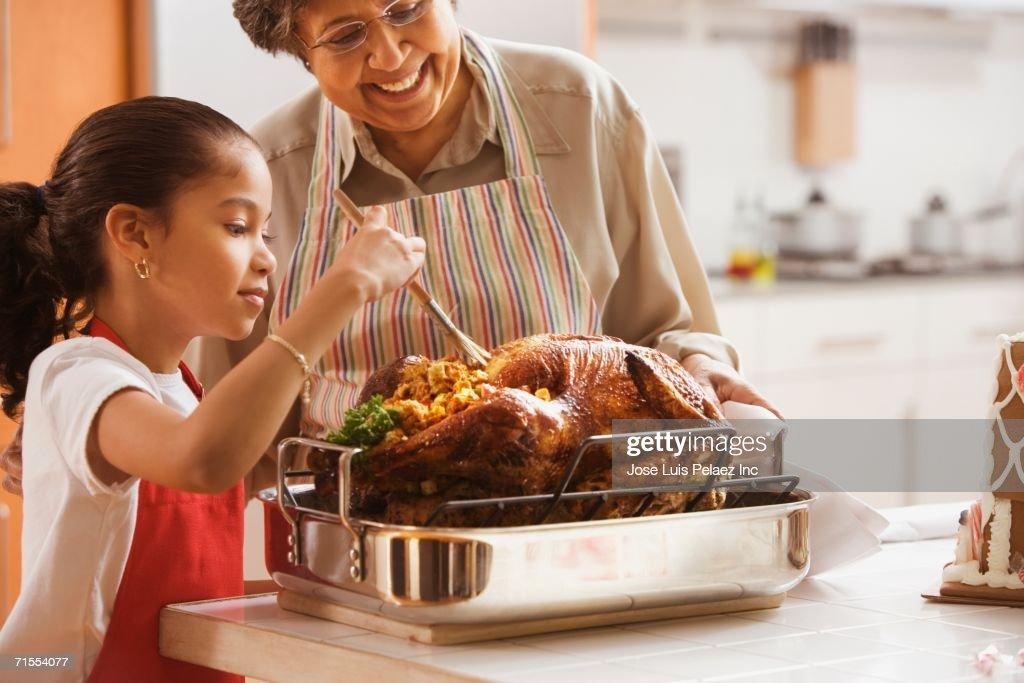Hispanic granddaughter helping grandmother baste turkey : Stock Photo