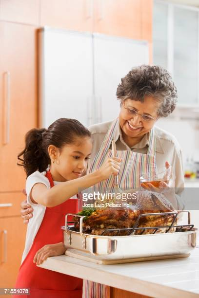 hispanic granddaughter helping grandmother baste turkey - happy thanksgiving text stock pictures, royalty-free photos & images
