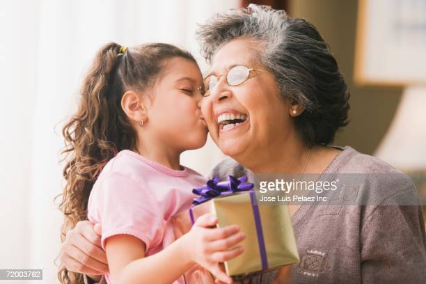 Hispanic granddaughter kissing grandmother and holding gift