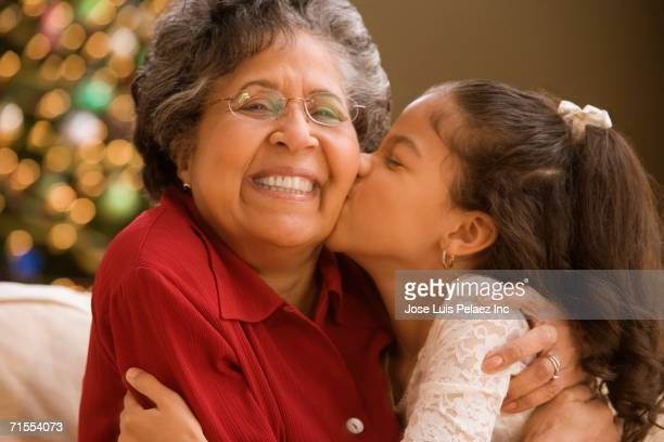 Hispanic granddaughter kissing grandmother