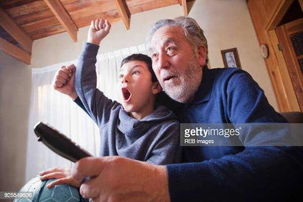 hispanic grandfather and grandson cheering for soccer game on television - family watching tv stock pictures, royalty-free photos & images