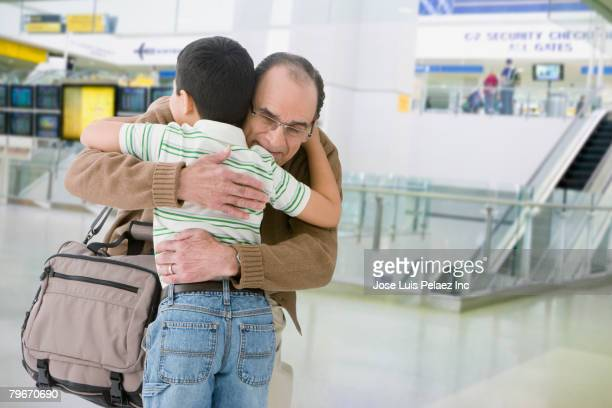 Hispanic grandfather and grandson hugging in airport