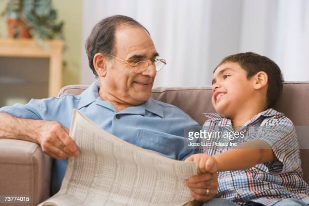 Hispanic grandfather and grandson reading newspaper on sofa